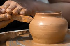 Hands of a street potter make a clay pot on a potter`s wheel. Close-up royalty free stock image