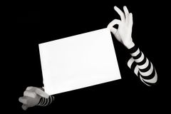Hands in striped gloves hold a white blank page Royalty Free Stock Photos