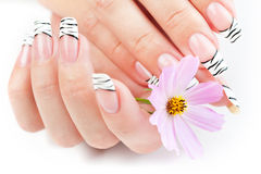 Hands with striped manicure relaxing with flowers Royalty Free Stock Images