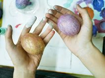 In the hands of the student painted eggs for Easter, background palette, art school workshop. Preparation for the holiday of Easter stock photos