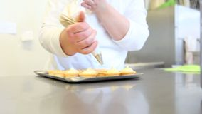 Hands stuffing pastry cream sweets. Chef hands stuffing pastry cream sweets stock video footage