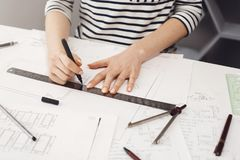 Hands of successful young female architect in striped shirt sitting at white table in home, making drawings with pen and. Ruler, doing project of her future stock image