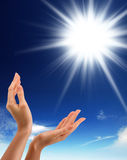 Hands, sun and blue sky with copy space Stock Images
