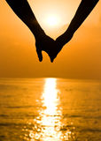 Hands at sunset. Young couple holding hands at sunset Stock Photography