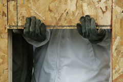 Hands Supporting a Wall. Construction worker's hands using the window opening to support a wall during installation at a construction site Stock Photo