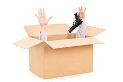 Hands surrendering gun and peeking from a box Stock Image