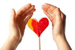 Hands surrounding lollipop heart Royalty Free Stock Photos