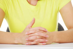 Hands on table with intertwined fingers Stock Photography