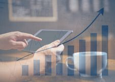 Hands with tablet in cafe and blue graph overlay Stock Photography