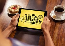 Hands with tablet showing black blog doodles against yellow background Royalty Free Stock Photo