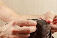 Hands of tailor sew durable cloth bag with needle close up stock images