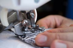Hands of tailor sewing clothes Stock Image