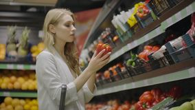 Hands take few colorful pepper one by one in marketplace and hold. Close up concept of selection, buy quality fruit or. Red vegetables. Young woman pick up some stock video footage