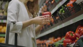 Hands take few colorful pepper one by one in marketplace and hold. Close up concept of selection, buy quality fruit or. Red vegetables. Young woman pick up some stock footage