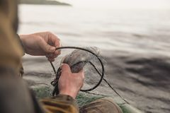 Fishing nets on a boat. Hands take fish out of a net Stock Photography