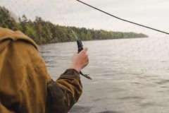 Fishing nets on a boat. Hands take fish out of a net Royalty Free Stock Photos