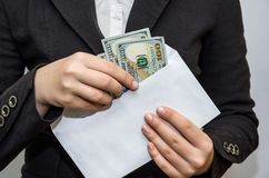 Female hands take out dollars from a white envelope. White background. royalty free stock photography