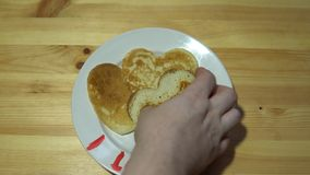 Hands take pancakes in the shape of heart with a white plate. Hands take pancakes in the shape of a heart with a white plate with a red inscription I love you stock video footage
