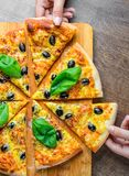 Hands take a slice of Pizza with Mozzarella cheese, Tomatoes, pepper, olive, Spices and Fresh Basil. Italian pizza. Pizza Margheri. Ta or Margarita on wooden royalty free stock image