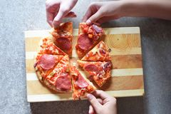 Hands take slices of pizza stock image
