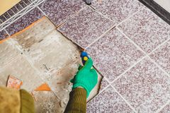 Hands take tile with chisel. Dismantling of tile. Hands in green working gloves undermine the broken tile with a chisel royalty free stock photography