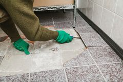 Hands take tile with chisel. Dismantling of tile. Hands in green working gloves undermine the broken tile with a chisel stock photos