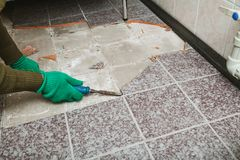 Hands take tile with chisel. Dismantling of tile. Hands in green working gloves undermine the broken tile with a chisel stock images