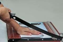 Hands take to cut the paper by using wooden guillotine paper trimmer . stock photography