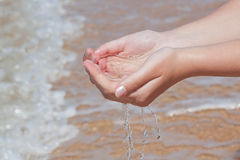 The hands take water into the sea. Stock Photo