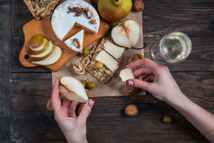 Hands takes peace of cheese and pear from table with food Royalty Free Stock Images