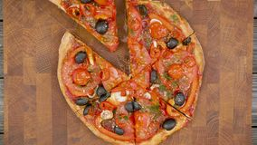 Hands takes slices of vegan pizza from the wooden plate, stop motion animation
