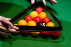 Hands taking away the triangle after setting up the balls. In pool Stock Photos