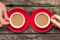 Hands taking cup of coffee on wood background Stock Photo
