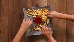 Hands taking french fries from a rotating plate stock footage