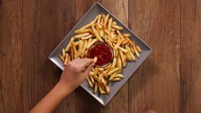Hands taking french fries from a rotating plate stock video