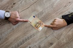 Hands take and give euro banknotes on wooden background royalty free stock photography