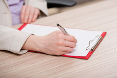 The hands taking notes in the pad Stock Photography
