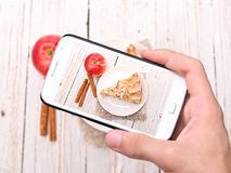 Hands taking photo apple cake with smartphone Stock Images