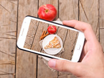 Hands taking photo apple cake with smartphone Royalty Free Stock Photo