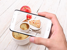 Hands taking photo apple cake with smartphone Stock Photography