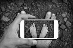 Hands taking photo bare legs with smartphone. Stock Image