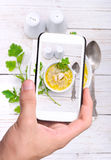 Hands taking photo chicken noodle soup with smartphone. Stock Photos