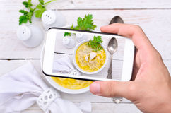 Hands taking photo chicken noodle soup with smartphone. Stock Images