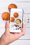 Hands taking photo cup of coffee with muffin with smartphone. Stock Image
