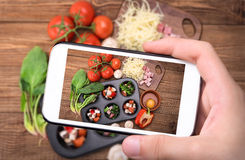 Hands taking photo egg muffins with ham, cheese and vegetables with smartphone. Stock Photos