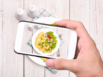 Hands taking photo egg omelette with smartphone Stock Photo