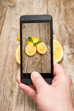 Hands taking photo of fruits on wooden. Stock Images