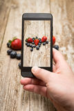Hands taking photo of fruits on wooden. Royalty Free Stock Images