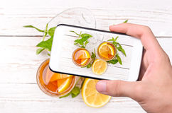 Hands taking photo ice tea with lemon with smartphone. Royalty Free Stock Images