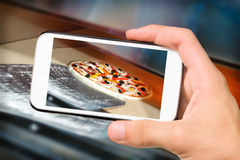 Hands taking photo pizza with smartphone Stock Images